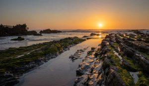 Sunset above tide rocks on Praia da Amoreira Portugal